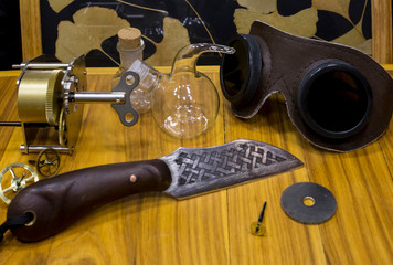 Still life in medieval style on a wooden table with an old knife, old glasses, a mechanism, gears and glass jars with Ginkgo Biloba leaves in the background