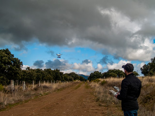 A drone pilot piloting with the remote control with smartphone in his hands in a dirt road in the forest
