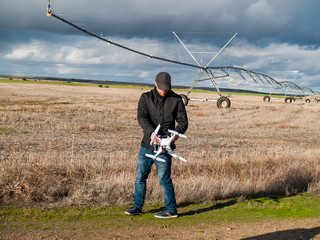 A drone pilot configuring his drone in a field with and irrigation system before flying