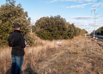 A drone pilot piloting with the remote control with smartphone in his hands in the forest near the train tracks