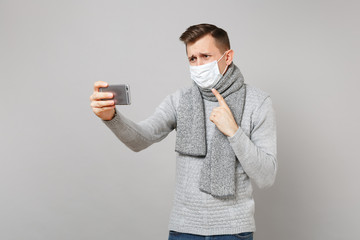 Young man in sweater, scarf sterile face mask making video call with mobile phone, pointing index finger on himself isolated on grey background. Health ill sick disease treatment, cold season concept.