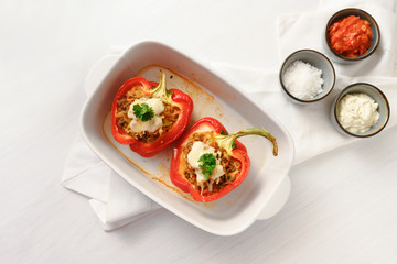 stuffed red bell pepper with cheese au gratin in a blue casserole dish on a white table, copy space, high angle view from above