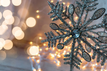 Silver beaded Christmas star with bokeh string lights background