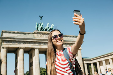 Young beautiful positive girl makes selfie against the background of the Brandenburg Gate in Berlin in Germany or takes pictures of sights.