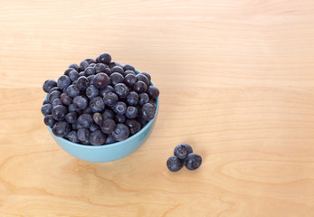 Blueberries in Blue Bowl on Table High Angle Isolated