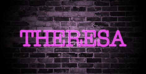 first name Theresa in pink neon on brick wall
