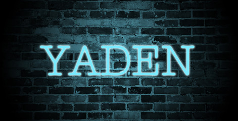 first name Yaden in blue neon on brick wall