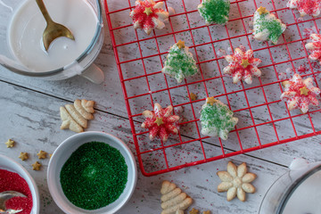 Homemade Royal icing Christmas sugar cookies with sprinkles on drying rack flat lay