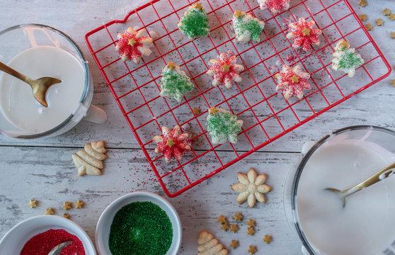 Homemade Royal icing Christmas sugar cookies with sprinkles on drying rack flat lay