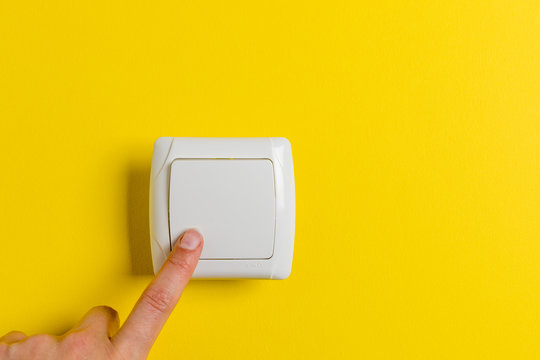 finger press light switch on a bright yellow background