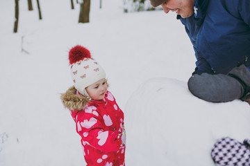 Cheery little girl in winter warm clothes hat playing, making snowball with dad in snowy park or forest outdoors. Winter fun, leisure on holidays. Love relationship family childhood lifestyle concept.