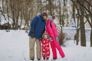 Young family kissing woman, man and little girl in warm clothes walking in snowy park or forest outdoors. Winter fun, leisure on holidays. Love childhood relationship family people lifestyle concept.