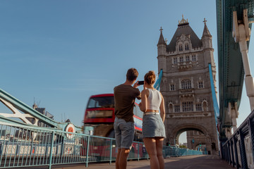 Foto op Aluminium Londen rode bus couple is taking a picture of a red double decker bus on the tower bridge in London