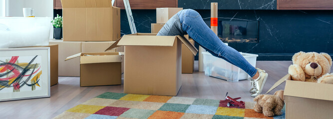 Young woman inside a box while preparing the move