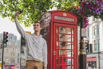 happy young boy taking a selfie in front of a phone box in Londond