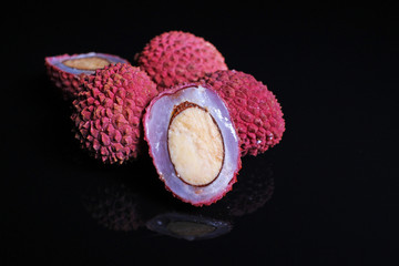 Lychee fruit whole grain fruits on black reflective background.