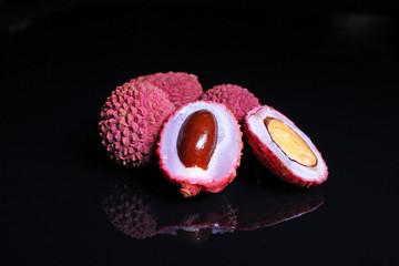 Lychee fruit whole grain fruits on black reflective background.