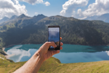 young man hand holding a smartphone and take a picture of an astonishing panorama