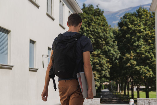 young man with backpack walking to school after summer holidays