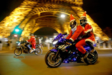 """People dressed in Santa Claus costumes ride on motorbikes near the Eiffel Tower during """"Carabalade"""" in Paris"""