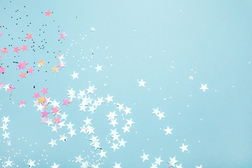 Silver and pink star glitter on blue pastel background. Festive concept. Place for design.