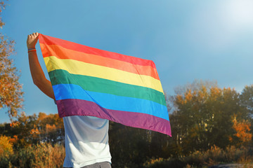Man with rainbow LGBT flag outdoors, space for text. Gay symbol