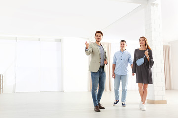 Real estate agent showing new apartment to young couple. Space for text