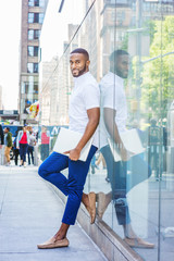 Young African American Man with beard, wearing white short sleeve shirt, blue pants, casual shoes, holding laptop computer, standing against glass wall on street in Manhattan, New York City,  smiling