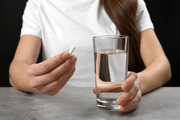 Woman holding pill and glass of water at table, closeup