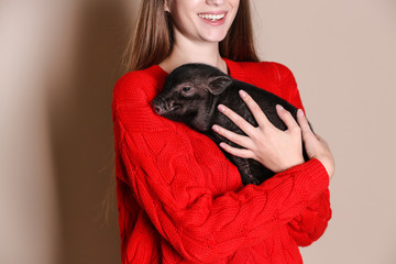 Woman holding mini pig on color background, closeup