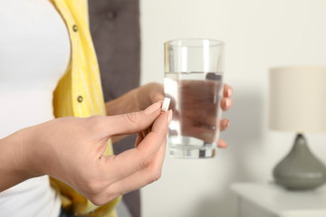 Woman with pill and glass of water indoors, closeup