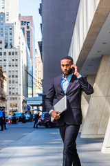Young African American businessman with beard talking on cell phone, traveling in New York, wearing black suit, carrying laptop computer, walking on street in Manhattan. Cars, buildings on background