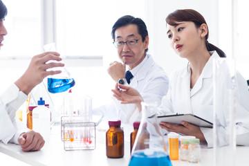 フラスコの中の青い液体に関して自分の意見を述べる女性研究員