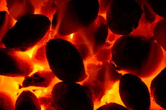 Burning glowing coal fire close-up background
