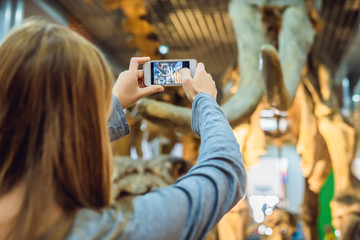 woman use mobile phone and blurred image of people in the dinosaur exhibition