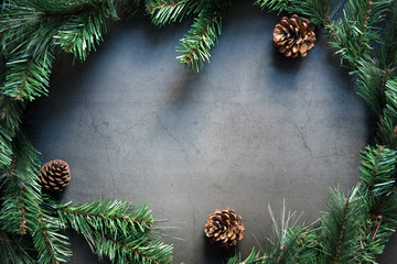 Fototapete - Christmas composition with frame of fir branches and pine cones on black background. Flat lay, top view.