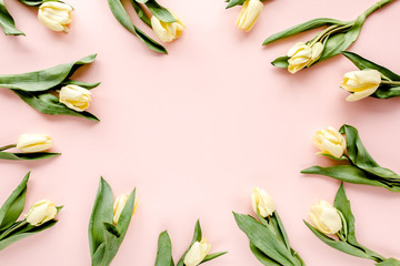 Frame of pastel and yellow tulip flowers bouquet on pink background. Flat lay, top view. Valentine's background. Floral pattern.