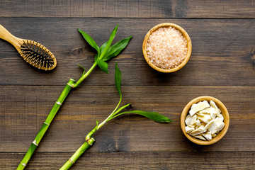 Asian spa background. Spa treatment concept. Bamboo branch, spa cosmetics on dark wooden background top view