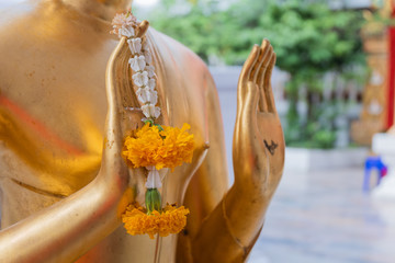 Close up Hand of The Buddha statue gold color hold flower garland in temple at thailand