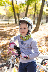 Cute little girl with a bicycle in the autumn forest