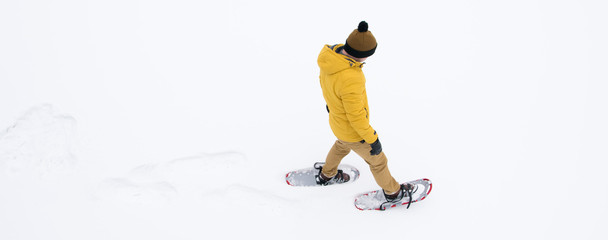 a man in winter, yellow clothes walking on white snow in snowshoes in the distance, there is a place for the inscription