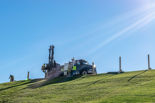Caucasian male Engineers working and operating a hydraulic telescopic truck mounted auger crane drill rig on a hill on a sunny summer day. Professional team of men hard at work in the field.