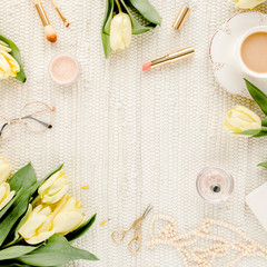 Female workspace with yellow tulip flowers, women's golden accessories, diary,  glasses on white background. Flat lay. Top view feminine background.