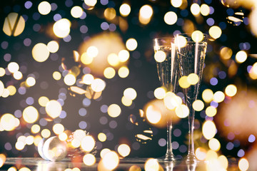 Wall Mural - Two glasses of champagne with Christmas toys. Festive lights bokeh background