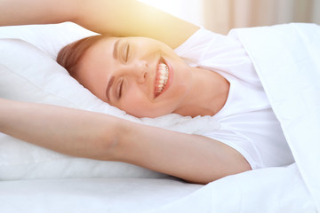 Beautiful young and happy woman stretching hands while lying in bed comfortably and blissfully smiling befor wake up in a morning. Sleeping concept