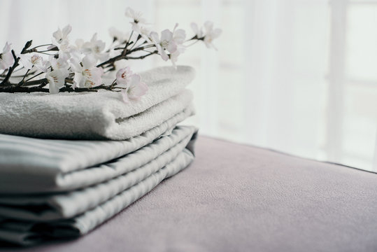 stacks grey white bed linen and towels textiles clothing with a brench of sakura. Fresh, comfort, spring, clean, aroma