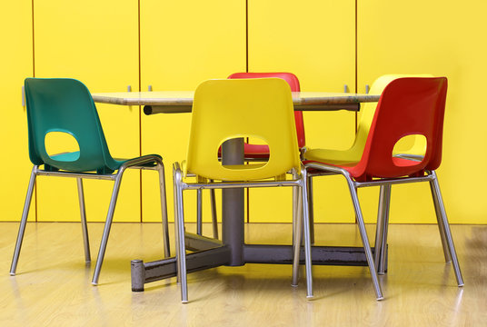 colored chairs around a table in a nursery school