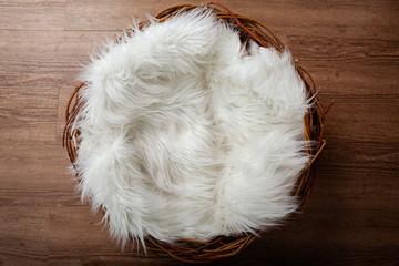 Wooden nest with white flufy sheepskin against an oak wooden floor