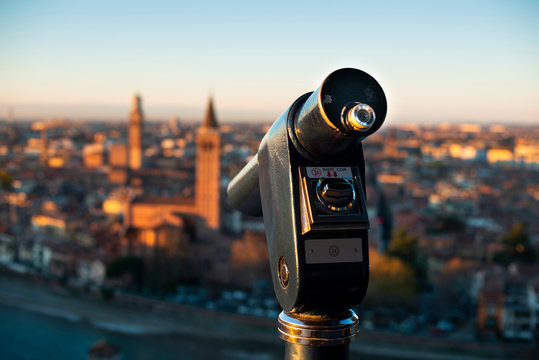 A close up photo of a public monocular on the top of a mountain with spectacular aerial views of the old city of Verona in Italy. Morning gold sunrise