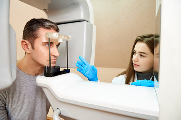The male patient is in the scanner, and the girl-doctor is near the control panel. Dental tomography. Treatment and prevention of oral cavity